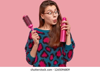 Attractive female wears big square glasses, stares with stupefaction at hairspray, holds hairbrush, wants to make coiffure for special occasion, models over pink background, going to fixate hair