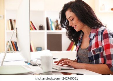 Attractive female working at home.She writing a blog in her bright living room.