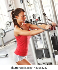 Attractive female working on her chest and arms at the gym.