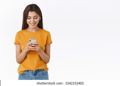 Attractive feminine young woman with long hair wear wireless earphone, smiling and laughing watching video in crowded cafe, look smartphone happy, listen music or pick song in playlist