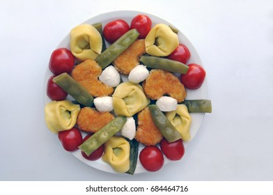 Attractive finger foods for dementia patients, eating with hands - fried chicken medallions, tortellini, cherry tomato, green beans and mozzarella