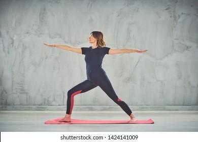 Attractive fit Caucasian brunette in sportswear doing Warrior II yoga pose on mat barefoot.