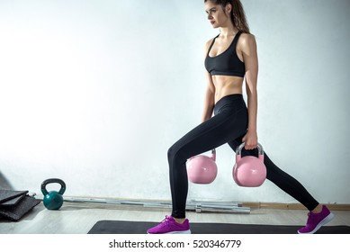 Attractive fit female doing lunge fitness exercise with pink rose kettlebell weight.
