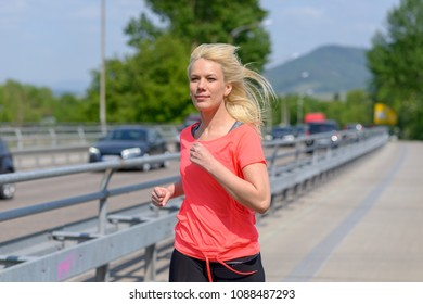 Attractive fit healthy woman out running or jogging approaching the camera across a pedestrian bridge alongside a motorway