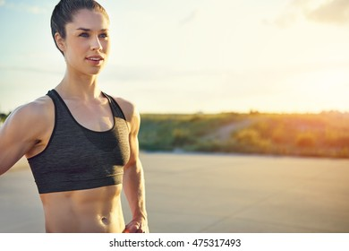 Attractive fit healthy young woman with a toned muscular body standing taking a pause from her workout in the glow of the rising sun