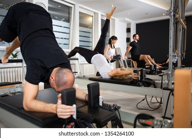 Attractive and fit males and females together practicing at the   gym studio using Pilates Tower Reformer