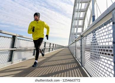 Attractive fit man running fast along big modern bridge. Exercising, Jogging, Sport, Winter. Male athlete running.