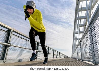 Attractive fit man running fast along big modern bridge. Exercising, Jogging, Sport, Winter. Male athlete running.