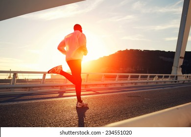 Attractive fit man running fast along big modern bridge at sunset light, black man doing workout outdoors, silhouette runner in windbreaker jogging over bridge road with amazing sunset on background