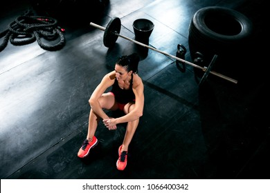 Attractive fit woman concetrate and resting at trainng at dark gym