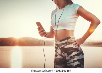 Attractive fit woman outdoors listening workout music