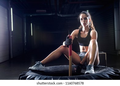 Attractive fit woman posing on tire with sledgehammer in fitness gym