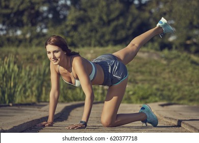 Attractive fit woman in summer sportswear doing the donkey kicks exercise for buttock muscles and legs, outdoors on a sunny summer day.