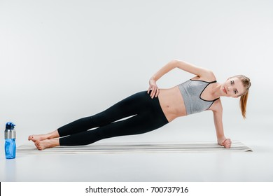 attractive fit young girl doing side plank exercise