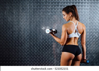 Attractive fitness woman with dumbbell indoor portrait, trained female body, studio caucasian model. Grey metal surface with a bumpy pattern background.