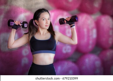 Attractive fitness woman with dumbbells, trained female body, lifestyle portrait, Asian model