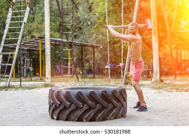 Attractive fittness man doing exercises outdoors. Sport, cross training outdoors. Muscular man training outdoors