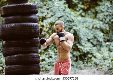 Attractive fittness man doing exercises outdoors. Sport,cross-fit. Training outdoors. Muscular man training outdoors