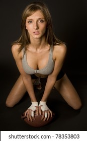 Attractive Football Player Kneeling Down Center Pose Leaning on Sports Ball