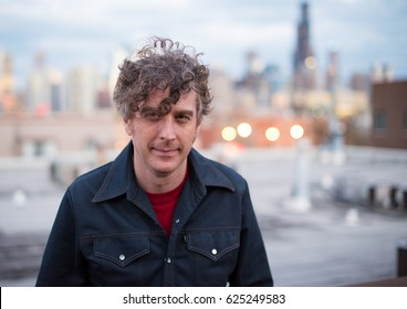 Attractive, forty something man, with long, curly brunette hair, on a rooftop, in the city, with cityscape in the distance. Dusk and sunset lights.