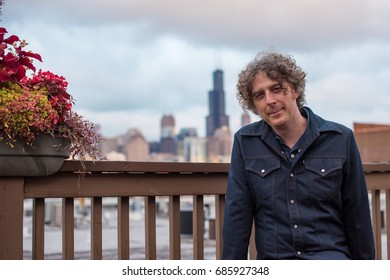 Attractive forty something man sitting on a rooftop deck in the city, with the Chicago skyline behind. He has long, curly salt and pepper hair and a nice smile.