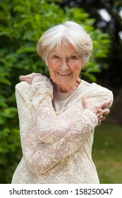 Attractive friendly elderly lady. Attractive friendly elderly lady with a lovely smile posing outside in a lush green garden in a stylish lacy blouse
