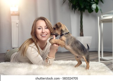 Attractive friendly woman cuddling with her small dog on a fluffy rug on a wood floor in the living room smiling happily at the camera