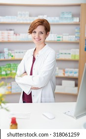 Attractive friendly young female pharmacist standing behind the counter in the pharmacy with crossed arms giving the camera a lovely warm smile