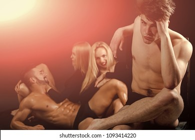 Attractive friends sitting on black background. Men with muscular body and twins, relations. men and twins women on black background, copy space