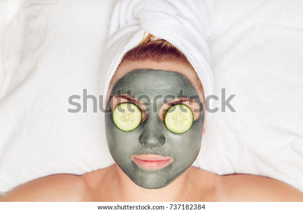 Attractive funny woman with a clay mask on her face. The concept of spa and skin care.