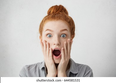 Attractive funny young female with bugged eyes and jaws dropped holding her face with both hands and shouting in surprise and full disbelief, shocked with big sale prices on online shopping websites