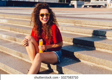 Attractive funny young woman in sunglasses sitting on steps, holds a bottle of fresh juice. Dressed in red blouse and jeans shorts, with long curly hair. Outdoors.