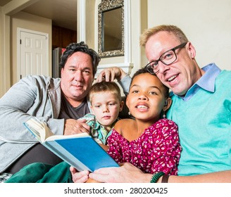 An attractive gay couple reads to their children in living room