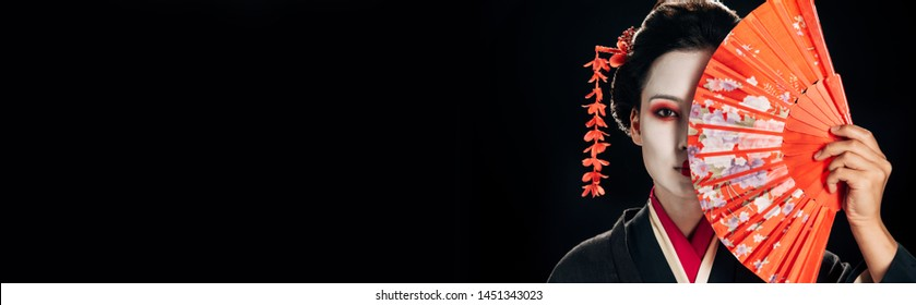 attractive geisha in black kimono with flowers in hair holding bright hand fan isolated on black, panoramic shot
