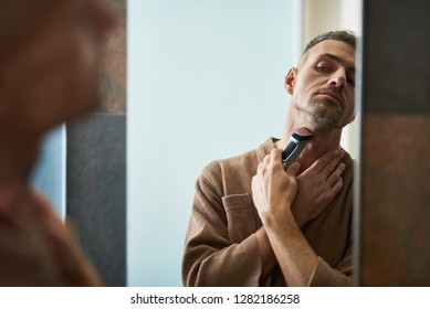Attractive gentleman in bathrobe removing stubble from neck with shaving machine while looking in the mirror