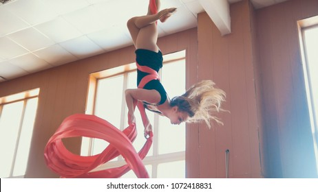 Attractive girl air gymnast hangs upside down and waving the aerial silk