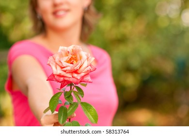 Attractive girl with beautiful red rose, against green summer garden.