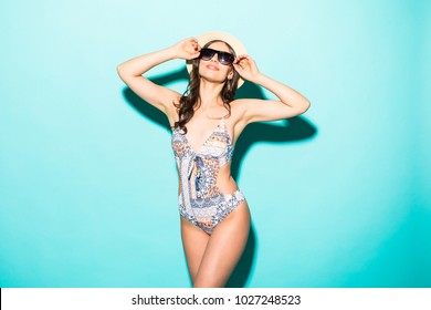 Attractive girl in bikini, hat, sunglasses, on a blue background with a perfect body.