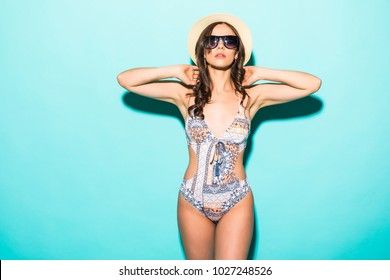Attractive girl in a bikini, hat, sunglasses on a bright blue background with a perfect body. Isolated. Studio shot.