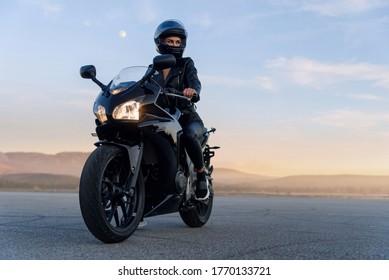 Attraktives Mädchen mit langen Haaren in schwarzer Lederjacke und Hose auf Parkplätzen mit stilvollem Sportmotorrad bei Sonnenuntergang.