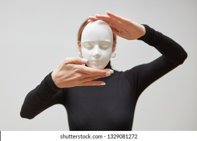 Attractive girl in a black sweater holds gypsum mask sculpture instead of face on a white background, place for text. Concept The masks we wear.