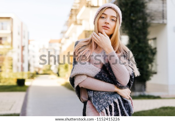 attractive girl with blond hair, wearing a warm hat, walking outdoors and posing