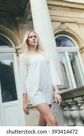 Attractive girl blonde with long hair, in white short dress, goes against the backdrop of an old house architecture.