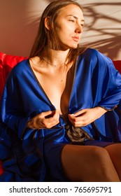 Attractive girl in a blue robe on a red sofa resting under a palm tree in the sun after a spa