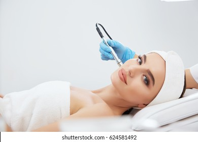 Attractive girl with brown hair fixed behind,clean fresh skin naked shoulders wearing white bath robe and hair bandage, doing cosmetic procedure at light medical background, microdermabrasion.