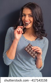 Attractive girl in casual clothes is eating a bar of chocolate, looking at camera and smiling, standing against dark background