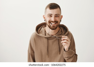 Attractive girl caught his attention. Portrait of entertained emotive young bearded man smiling cheerfully, biting rim of glasses and enjoying nice conversation, being interested and joyful