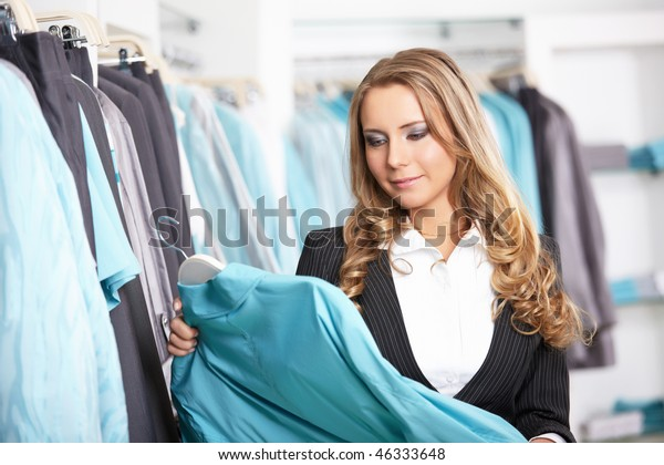 The attractive girl chooses clothes in shop