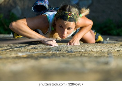 Attractive girl climbs a granite rock