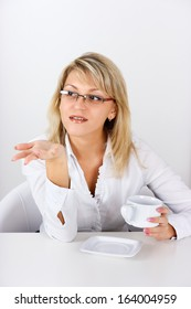 An attractive girl with a cup in the office gesticulates